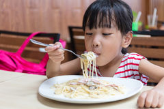 Asian Chinese little girl eating spaghetti Royalty Free Stock Photography