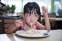 Asian Chinese little girl eating spaghetti. At outdoor cafe Stock Photo
