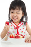 Asian Chinese little girl eating strawberries Royalty Free Stock Images