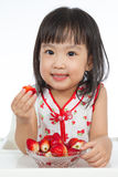 Asian Chinese little girl eating strawberries Royalty Free Stock Photo