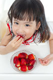 Asian Chinese little girl eating strawberries Stock Photography