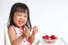 Asian Chinese little girl eating strawberries Royalty Free Stock Photos