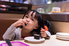 Asian Chinese little girl eating sushi at a Japanese restaurant Royalty Free Stock Images