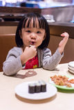 Asian Chinese little girl eating sushi at a Japanese restaurant Stock Photo