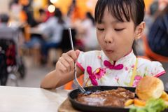 Asian Chinese little girl eating Western Food stock photos
