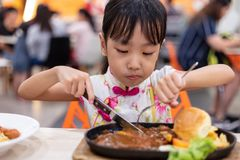 Asian Chinese little girl eating Western Food royalty free stock image