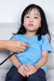 Asian Chinese little girl examine by doctor with stethoscope. In the hospital Stock Images