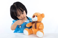 Asian Chinese little girl examine teddy bear with thermometer Stock Images