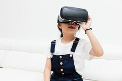 Asian Chinese little girl experiencing virtual reality at home. Asian Chinese little girl experiencing virtual reality with vr headset at home Stock Images