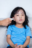 Asian Chinese little girl getting ear measurement for fever temp. Erature at home Stock Photo