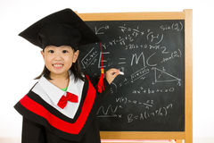 Asian Chinese little girl in graduation gown againts blackboard Royalty Free Stock Photography