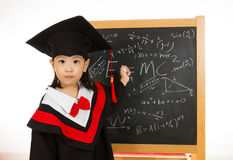 Asian Chinese little girl in graduation gown againts blackboard Stock Photography