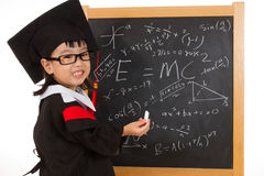 Asian Chinese little girl in graduation gown againts blackboard Stock Photos