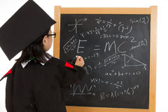 Asian Chinese little girl in graduation gown againts blackboard Royalty Free Stock Photo