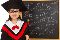 Asian Chinese little girl in graduation gown againts blackboard Royalty Free Stock Image