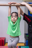 Asian Chinese little girl hanging on horizontal bar Royalty Free Stock Photo