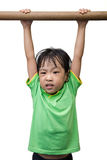 Asian Chinese little girl hanging on horizontal bar. In isolated white background Royalty Free Stock Images