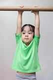 Asian Chinese little girl hanging on horizontal bar Royalty Free Stock Images