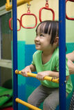 Asian Chinese little girl hanging on rings. At indoor playground Royalty Free Stock Photography