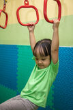 Asian Chinese little girl hanging on rings. At indoor playground Royalty Free Stock Image