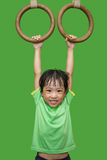 Asian Chinese little girl hanging on rings stock photos