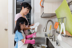 Asian Chinese little girl helping mother washing dishes. In the kitchen at home Stock Images