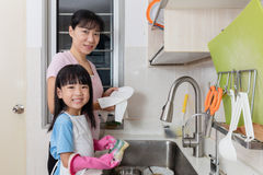 Asian Chinese little girl helping mother washing dishes. In the kitchen at home Royalty Free Stock Photography