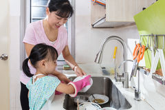 Asian Chinese little girl helping mother washing dishes. In the kitchen at home Royalty Free Stock Photos