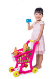 Asian Chinese little girl holding credit card with shopping trol. Ley full of vegetables in isolated white background Stock Photos