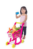 Asian Chinese little girl holding credit card with shopping trol. Ley full of vegetables in isolated white background Royalty Free Stock Photos