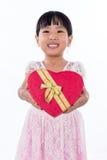 Asian Chinese little girl holding heart shape gift box Stock Photo