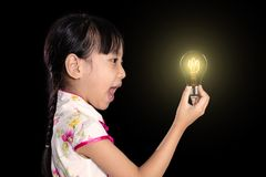 Asian chinese little girl holding a light bulb royalty free stock image