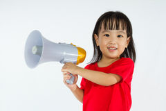 Asian Chinese little girl holding megaphone. Portrait of a young little Chinese girl holding a megaphone in isolated white background Royalty Free Stock Photo