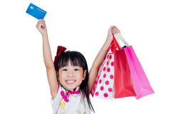 Asian Chinese little girl holding shopping bags with credit card Royalty Free Stock Photos