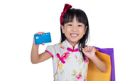 Asian Chinese little girl holding shopping bags with credit card Stock Photo