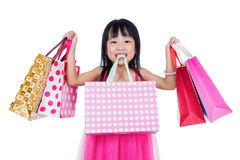 Asian Chinese little girl holding shopping bags. In isolated white background royalty free stock photos