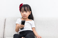 Asian Chinese little girl holding a TV remote control Stock Images