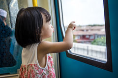 Asian Chinese little girl inside train looking beside the window Royalty Free Stock Photo