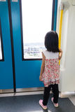 Asian Chinese little girl inside train looking beside the window Royalty Free Stock Image