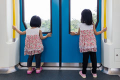 Asian Chinese little girl inside train looking beside the window Stock Photography