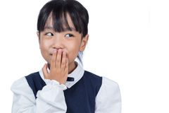Asian Chinese little girl laughing and covering her mouth. In isolated white background Stock Photos