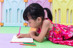 Asian Chinese little girl laying on the floor coloring Stock Photos
