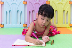 Asian Chinese little girl laying on the floor coloring Stock Photography