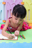 Asian Chinese little girl laying on the floor coloring Stock Images