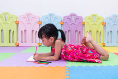 Asian Chinese little girl laying on the floor coloring Royalty Free Stock Image