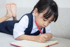 Asian Chinese little girl laying on the sofa writing book. In the living room Stock Photography