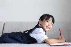 Asian Chinese little girl laying on the sofa writing book. In the living room Royalty Free Stock Photo