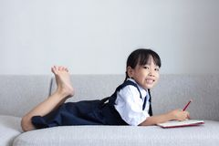 Asian Chinese little girl laying on the sofa writing book. In the living room Royalty Free Stock Photos