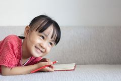 Asian Chinese little girl laying on the sofa writing book. In the living room Stock Photos