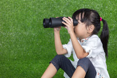 Asian Chinese little girl looking through binoculars. Asian Chinese little girl sitting on the grass and looking through binoculars at outdoor park stock photo